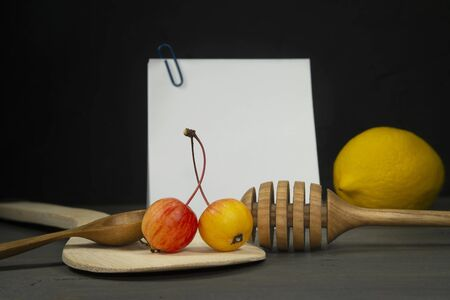 Recipe concept with wild apples, wooden spoon, lemon and honey wand with sticky notes on a gray old wood surface against a dark wall in grunge style, free space for text Stockfoto