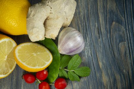 Natural remedies for cold and flu season with fresh root ginger, lemon, garlic and rose hips on a rustic wooden table