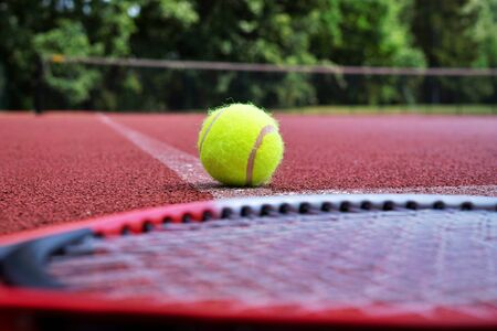 Low angle view tennis scene with ball, racquet and hard court surface corner line Stockfoto