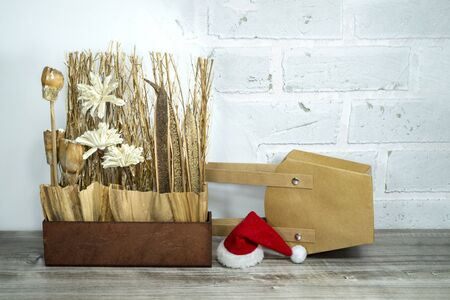 Christmas still life with colorful red Santa Hat, decorations and kraft paper bag over a white brick wall with copy space for a seasonal greeting