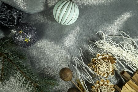 Christmas decorations with cones, fir branch and softly draped silver grey fabric in a seasonal still life to celebrate the holiday season Stockfoto