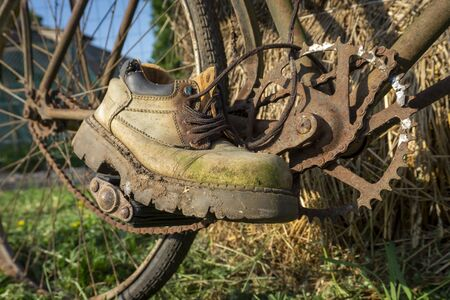 Pair of old worn leather hiking boots on a rusty vintage bicycle outdoors balanced on the pedals as though riding it Stockfoto