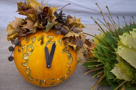 Autumn still life with colorful pumpkin clock with carved numerals decorated with assorted fall leaves conceptual of the seasons