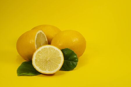 Whole and halved ripe lemon fruit with green leaves on yellow background Imagens