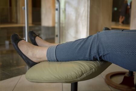 Overweight woman with her feet up in casual flat shoes on a padded stool in a close up on her legs