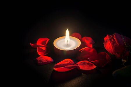 Tea candle and red rose petals with shallow depth of focus with reflection on black background