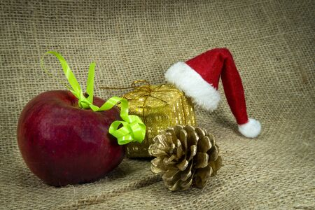 Christmas still life with colorful red Santa Hat, decorations, gold wrapped gift and apple over a hessian or burlap background with copy space for a seasonal greeting Imagens