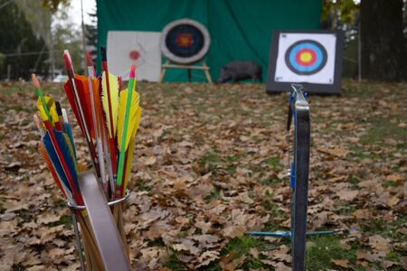 Colorful archery arrows and targets outdoors in an autumn park with fallen leaves on the grass in a sporting or conceptual image Stockfoto