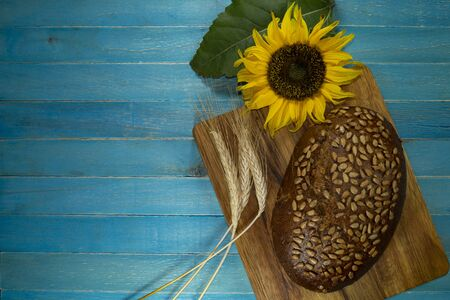 Bread with sunflowers seeds, ear of ripe wheat and sunflower blossom on wooden cutting board Stockfoto