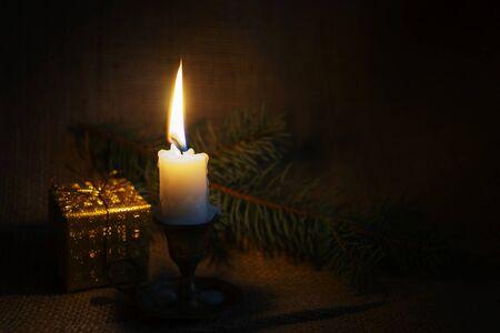 Kerstachtergrond met brandende kaars, cadeau en spartak op rustieke juteachtergrond met kopieerruimte voor een vakantiegroet Stockfoto