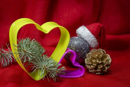 Close-up on Christmas decorations and plastic heart-shaped cookie cutters sitting on red cloth background