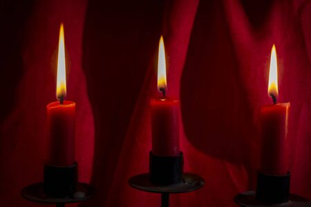 Three burning red candles against velvet drapes conceptual of prayer, celebration, Christmas or Advent