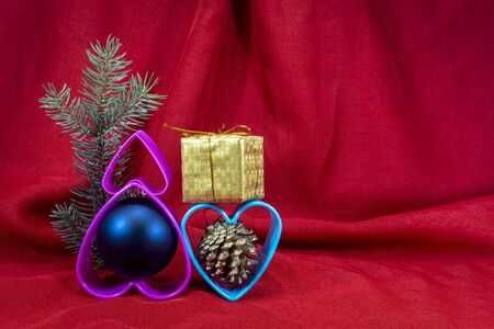 Christmas decorations with plastic hearts and small golden present box on red fabric background with copy space