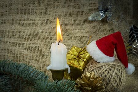 Christmas background with burning candle, decorations, gift, ball of twine and Santa hat on rustic burlap background with copy space for a holiday greeting