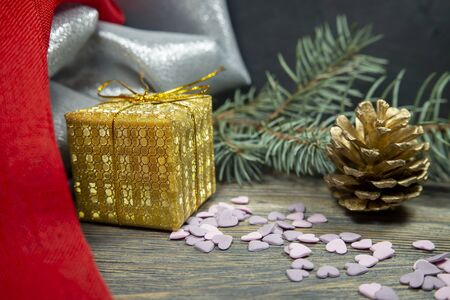 Festive Christmas background with golden gift and cone with a pine branch, colorful red drape and assorted decorations Stockfoto