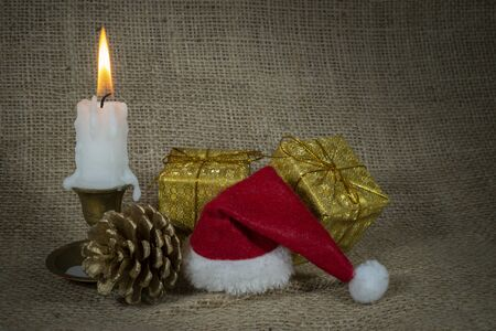 Christmas still life with burning candle, pine cones, gold wrapped gifts and Santa hat on a hessian background with copy space for a holiday greeting