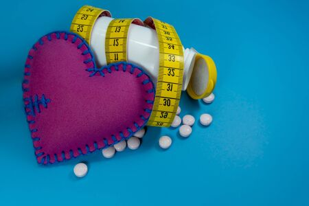 Medicine pills spilling out of a white bottle wrapped around with measuring tape near heart sing on a blue background. Healthcare, diet or weight loss concept Imagens