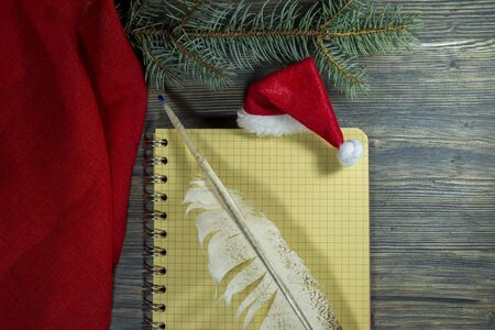 Red Santa hat with quill pen and spiral bound notebook decorated with a border of red fabric and pine branch for Christmas themed concepts