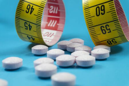 Medicine pills and measuring tape on blue background. Healthcare, diet or weight loss concept Imagens