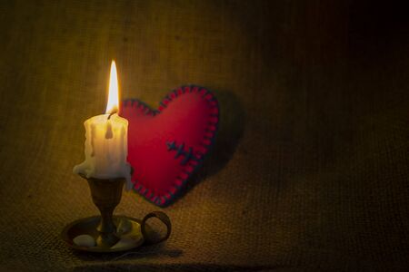 Burning candle on a vintage candlestick and a small red stitched fixed broken heart in the dark against sack cloth background with copy space. Magical love spell concept