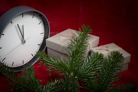 Christmas still life with a clock , gifts and pine branches over a festive red background with vignette and copy space for a seasonal greeting
