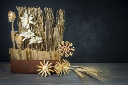 Rustic Christmas still life with handcrafted decorations of natural seeds, grasses and flowers over a grey background with copy space