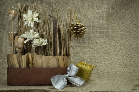 Christmas still life with gold wrapped gift, decorations over a hessian or burlap background with copy space for a seasonal greeting