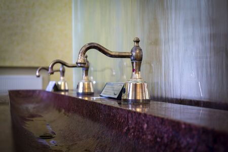 Antique copper faucets and marble sink, viewed in close-up Standard-Bild