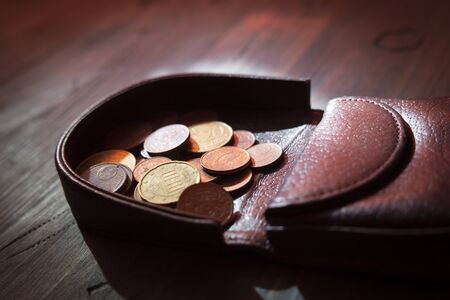 Euros coins change in open dark brown hard leather coin case tray purse or wallet, viewed in close-up on wooden table