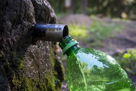 Filling a green plastic clean fresh water bottle at a fountain pipe set into a rock outdoors in the countryside in a close up view Stock Photo