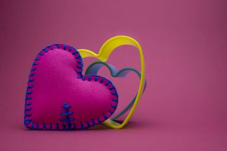 Romantic still life with hand sewn textile pink heart and nested colorful hearts shapes on pink with copy space for a message to your sweetheart Banco de Imagens