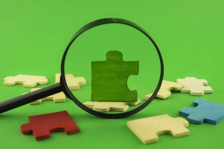 Colorful jigsaw puzzle pieces with magnifying glass focused on a single green corner piece in a conceptual image over green for search, investigation and problem solving