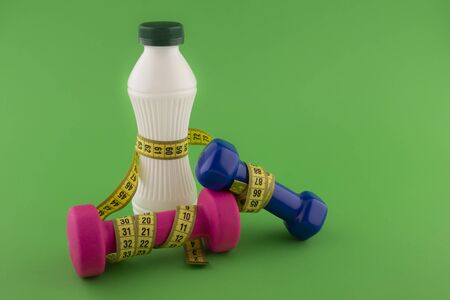 Weight loss and fitness concept with tape measure wound round a white plastic bottle with a slim line shape, pink and blue dumbbells on green chroma key background