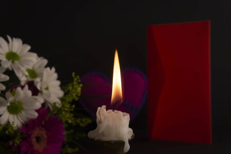 Short candle burning on the floor in close-up among flowers, next to red envelope against dark background. Romantic evening theme concept