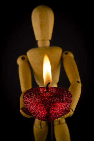 Wooden puppet or figure holding a burning red candle over a dark background in a conceptual image