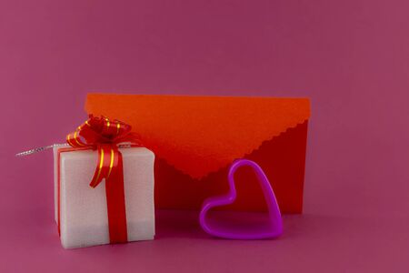Romantic still life with purple glowing heart, decorative gifts and red envelope on pink background with copy space