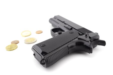 Gun and euro coins on a white background, robbery or gun cost concept Imagens