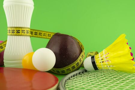 Table tennis, badminton sports and healthy nutrition concept still life on green chromakey background in close-up