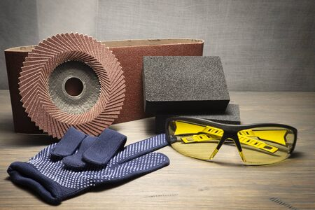 Various grinding tools - sanding belt, abrasive sponge and flap disc for angle grinder, safety gloves and goggles, renovation, safety and health at work concept Imagens
