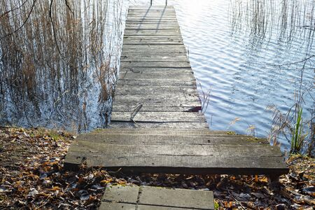 Old rustic wooden steps leading to a jetty over the calm water of a lake with reeds looking down from the top Imagens