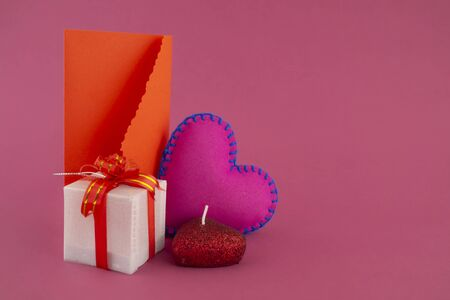 Romantic still life with hand sewn textile pink heart, candle, decorative gifts and red envelope on pink background with copy space Banco de Imagens