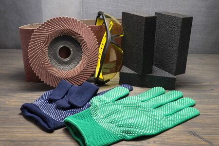 Various grinding tools - sanding belt, clamps, abrasive sponge and flap disc for angle grinder, safety gloves and goggles, renovation, safety and health at work concept