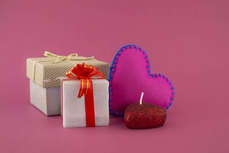 Romantic still life with hand sewn textile pink heart, candle, decorative gifts and red envelope on pink background with copy space