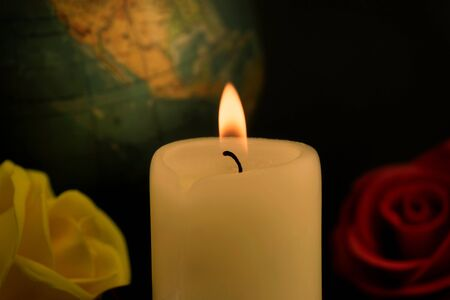 Single burning yellow candle in front of a globe next to red and yellow roses against dark background, concept of global disasters and deaths
