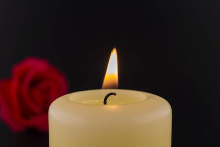 Single burning yellow candle next to red rose against dark background Foto de archivo