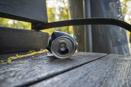 Crumpled can lying on the seat of a rustic wooden a park bench in a low angle close up view