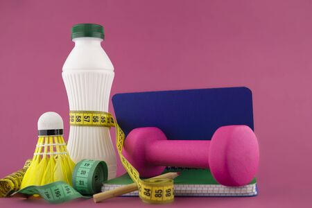 Sport weight loss and fitness concept with a shuttlecock, dumbbell weight and tape measure wound round a white plastic bottle with a slim line shape, open notebook with pen on a bright pink background