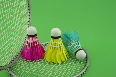 Badminton rackets and colorful feathered shuttlecocks in blue, yellow and pink on green background in a close up view Foto de archivo