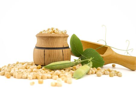 Dried peas spilling from a wooden barrel and fresh plant with pods isolated on a white background Banque d'images