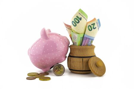 Rolled Euro banknotes in a barrel with a little ceramic pink piggy bank and loose coins over a white background with copy space for savings, finances or money related themes